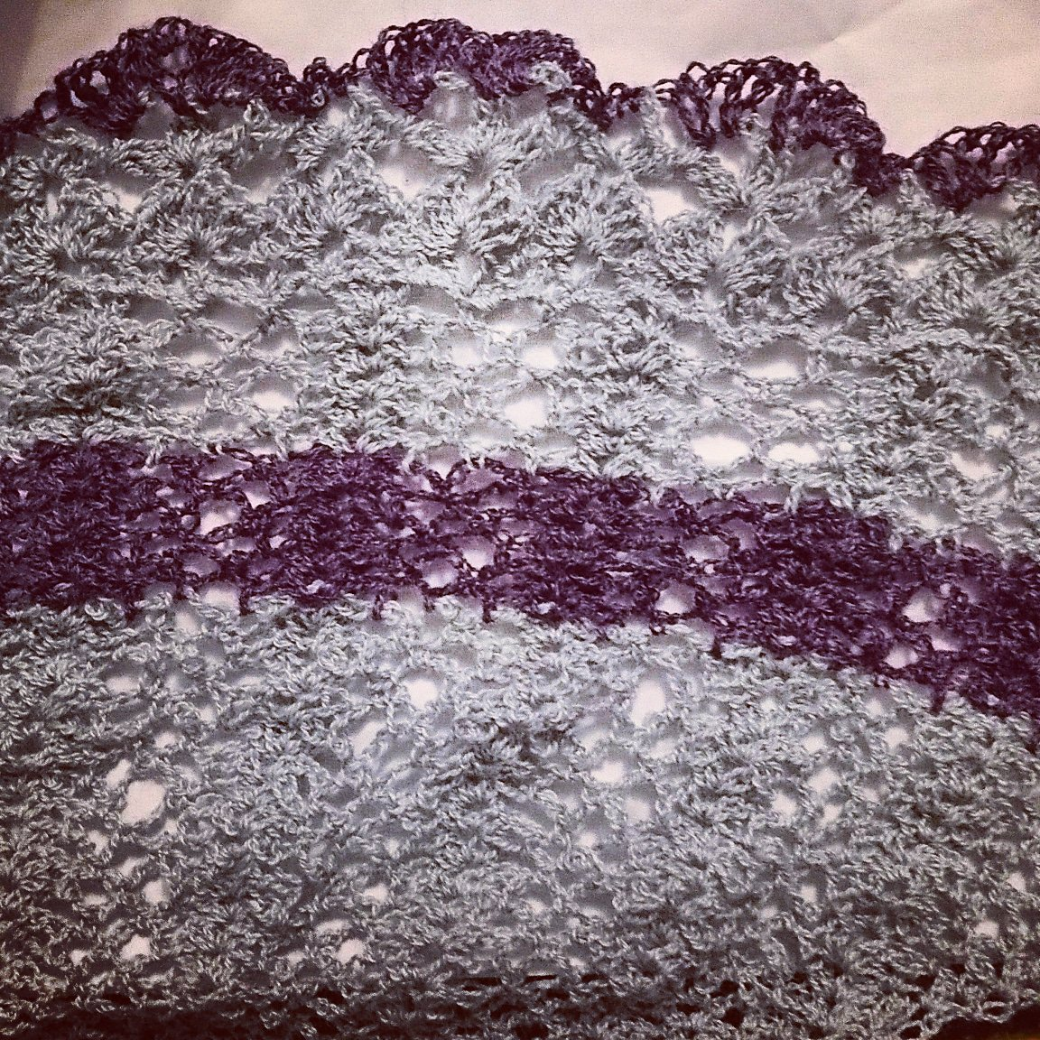 Finished shawl, with stripe of purple and lace edge ending in purple