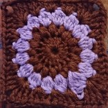 Granny square in brown and pink, with a circle in the square