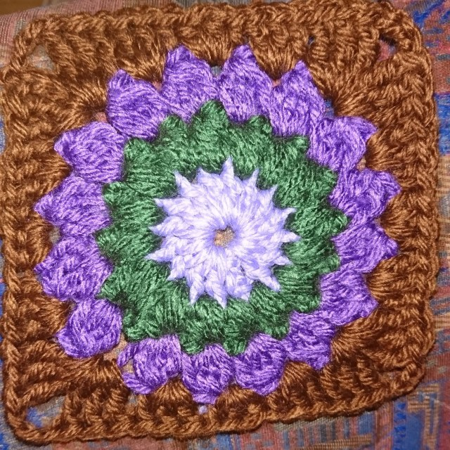 Starburst granny square in lilac, green, purple and brown